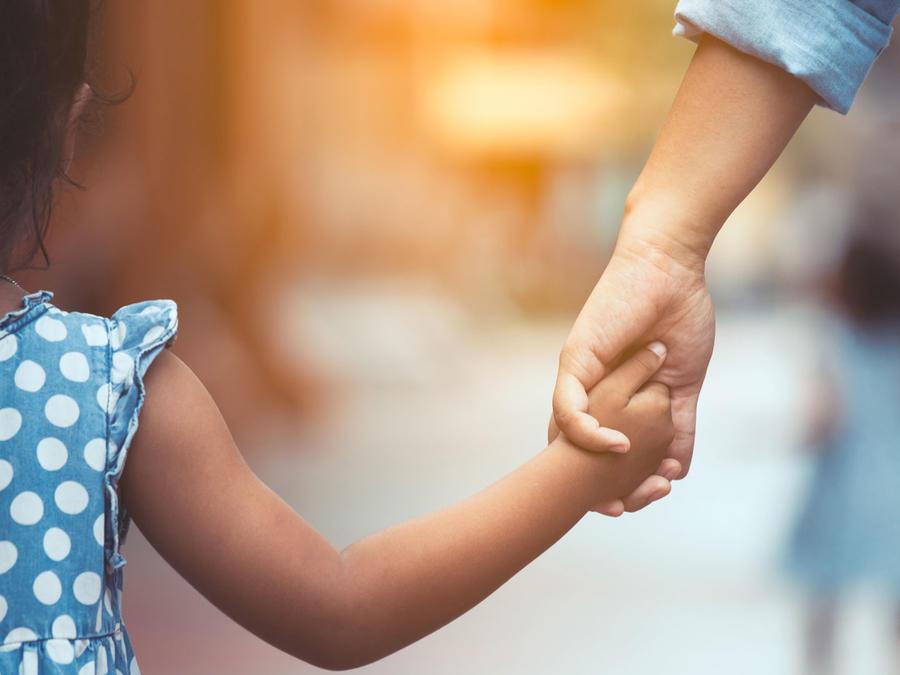 Niña pequeña, de la mano de su mamá