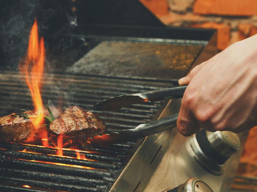 Hombre preparando carne a la parrilla