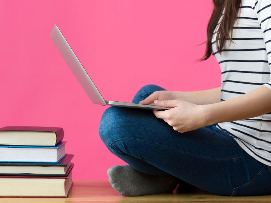 Chica sentada estudiando, con computadora