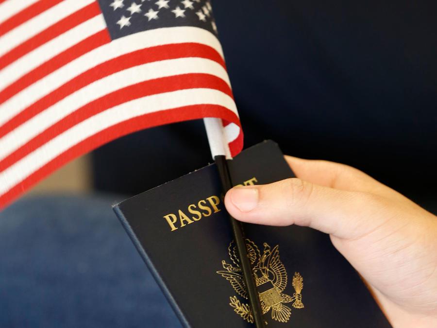 Una persona con un pasaporte de EEUU y una mini bandera