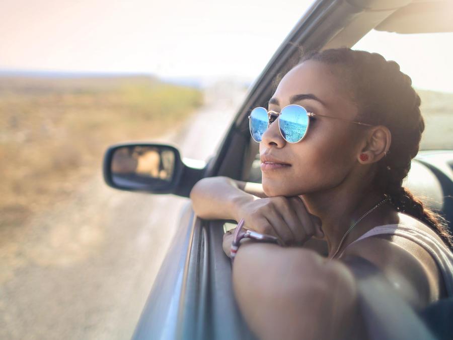 Joven latina mirando por la ventana del coche