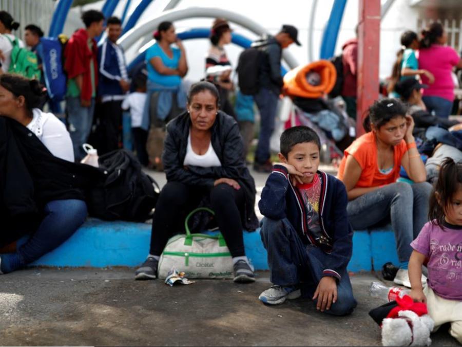 Migrantes esperan en fila este jueves para ingresar a un centro deportivo, que actualmente se usa como refugio temporal, en Tijuana, México.