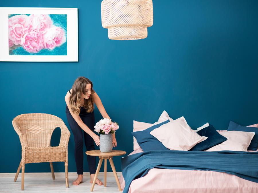 Mujer decorando su habitación llena de colores vibrantes.