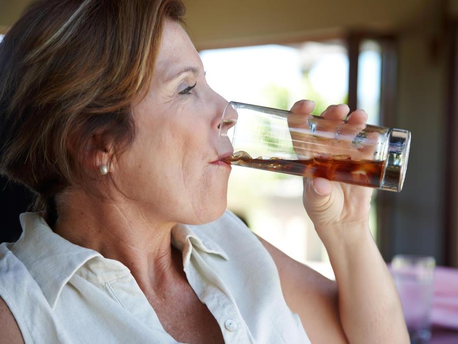 Mujer bebiendo refresco.