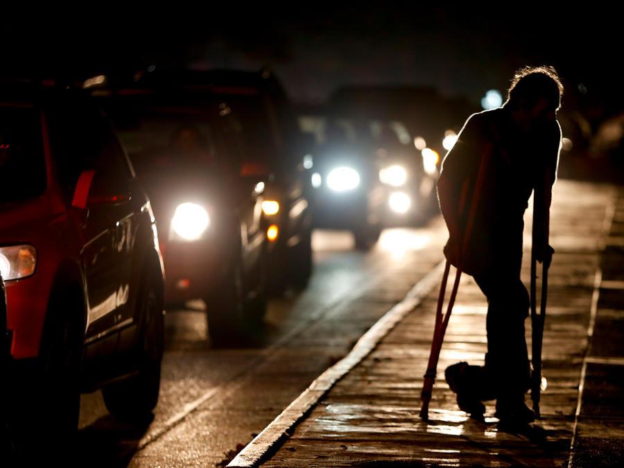 Una persona cruza una calle en Venezuela en medio de los cortes eléctricos