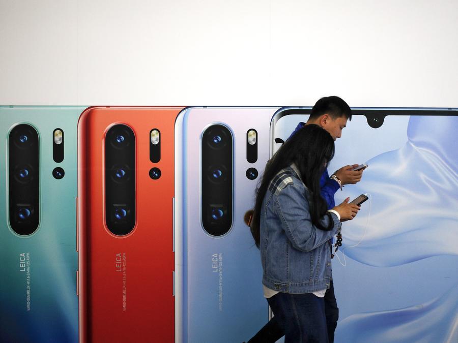 Una pareja china mira sus teléfonos mientras pasa por un anuncio de la compañía de celulares Huawei