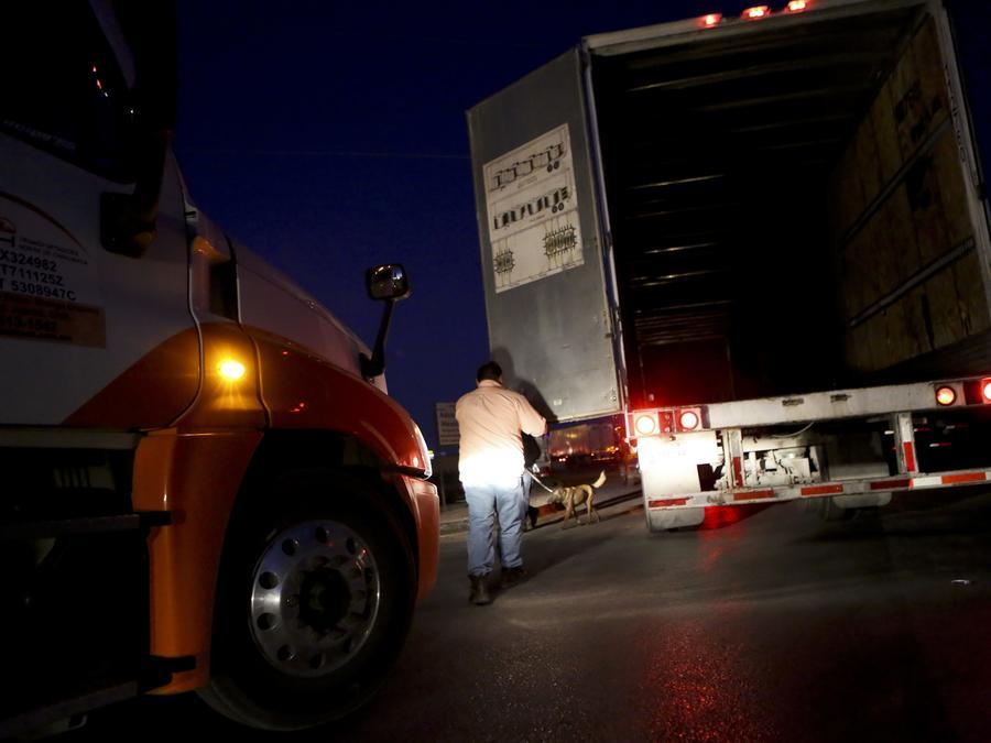 En esta fotografía de archivo del 9 de abril de 2019, un guardia de seguridad en la frontera con México revisa la carga de un camión
