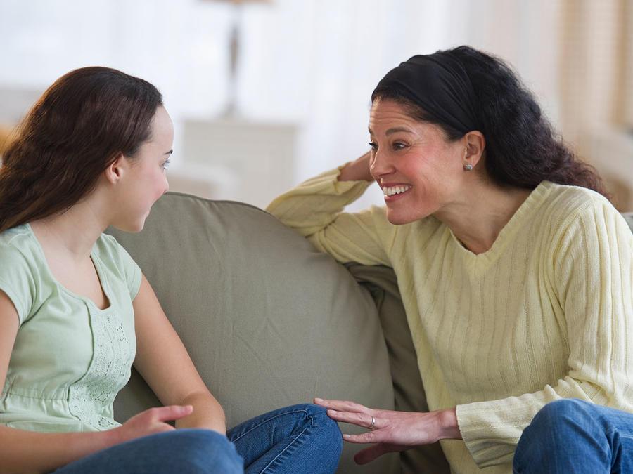 Madre e hija sentadas en el sofá