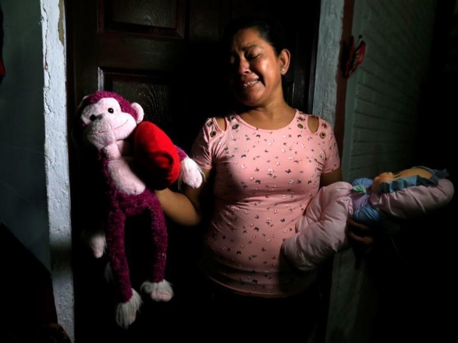 Rosa Ramírez solloza muestra a los periodistas los juguetes de su nieta Valeria, de casi 2 años, en su casa de San Martín, El Salvador, el martes 25 de junio de 2019.