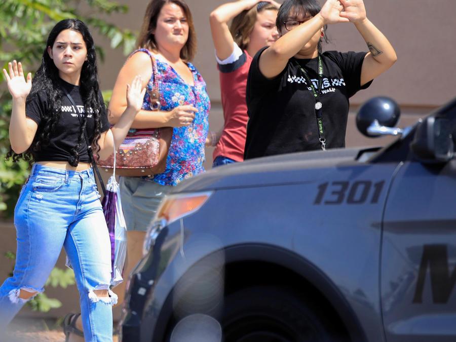 Personas con las manos en alto en la escena del tiroteo en un Walmart en El Paso, Texas, hoy