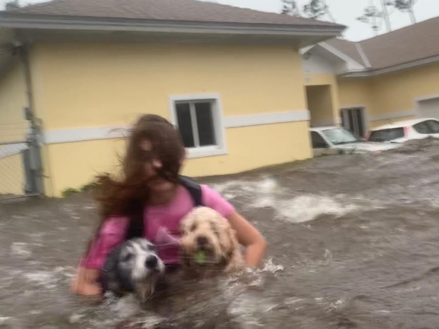 Julia Aylen, una residente de Freepor Bahamas, vadea el agua profunda mientras carga a sus mascotas para sacarlas de su hogar inundado