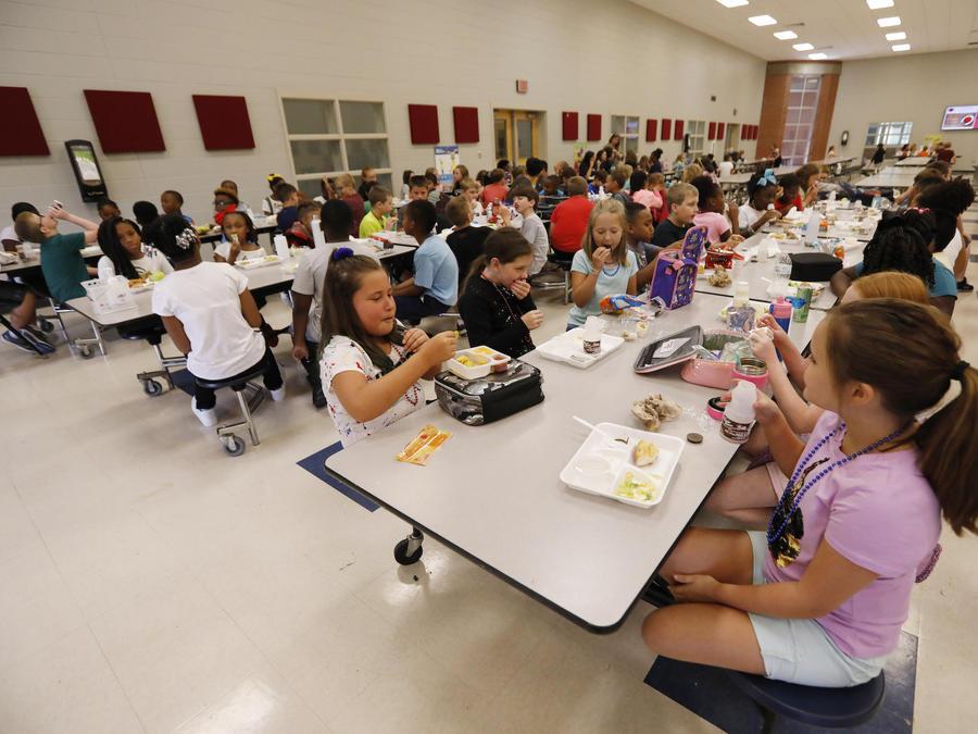 Imagen de archivo de niños comiendo en una cafetería escolar.