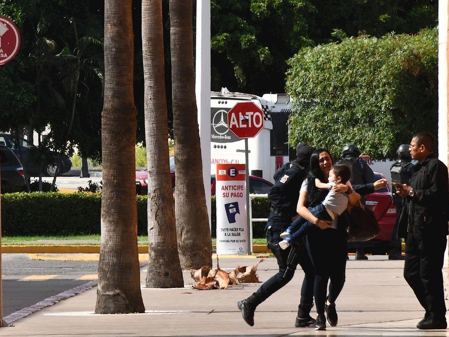 Transeúntes huyen en el medio de fuerte enfrentamientos entre grupos armados y fuerzas de seguridad el pasado jueves en Culiacán (México).