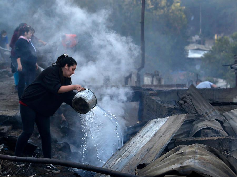 Una mujer sofoca las llams de los escombros en los que acabó una vivienda tras incendios en el norte de Chile entre este martes y miércoles.