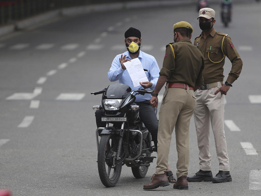 Un hombre en motocicleta muestra sus papeles a dos policías durante la cuarentena en Jammu, India.