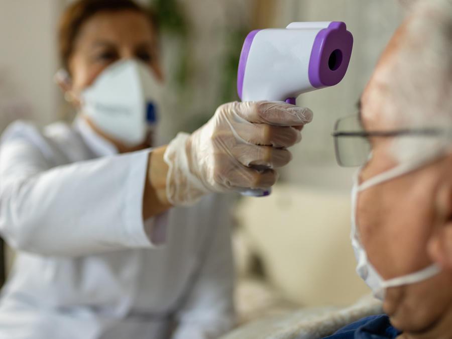 Una enfermera le toma la temperatura a un anciano en una imagen creativa.