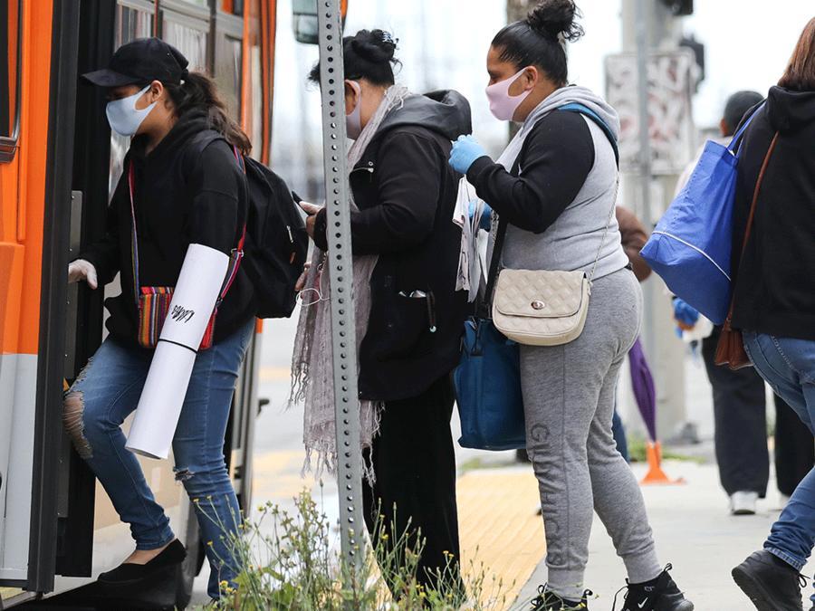 Pasajeros subiendo a un bus público en Los Ángeles durante el coronavirus