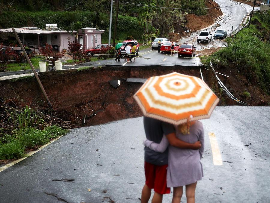 Un hombre y una mujer frente a una sección de una carretera que colapsó y continúa erosionándose días después de que el huracán María azotara la isla, octubre de 2017 en Barranquitas, Puerto Rico.
