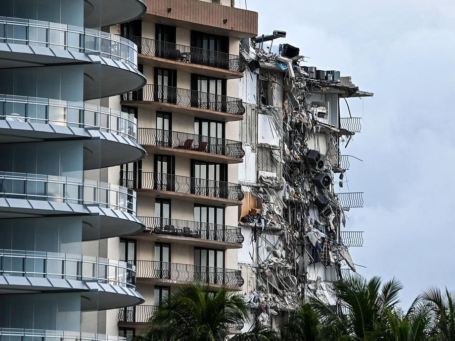 Escombros cuelgan de un edificio parcialmente derrumbado en Surfside al norte de Miami Beach, el 24 de junio de 2021.