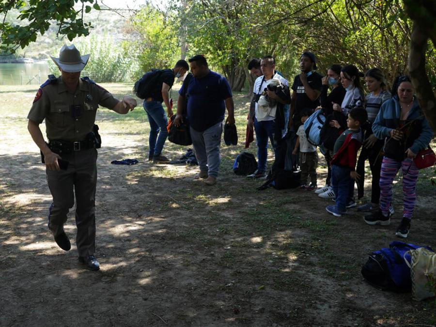 Agentes del Departamento de Seguridad Pública de Texas atienden a un grupo de migrantes que cruzaron la frontera
