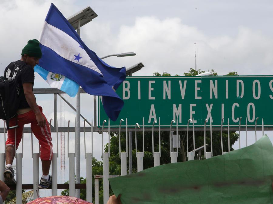 Un hombre subido en la reja de entrada a México, ubicada en el puente de Ciudad Hidalgo, sobre el río Suchiate. Miles de migrantes que van en caravana rumbo a EEUU esperan el 19 de octubre que las autoridades mexicanas les permitan entrar.