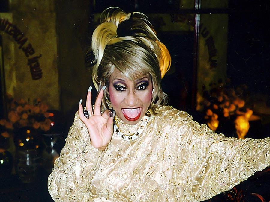 Celia Cruz con peluca amarilla y uñas postizas gritando azúcar