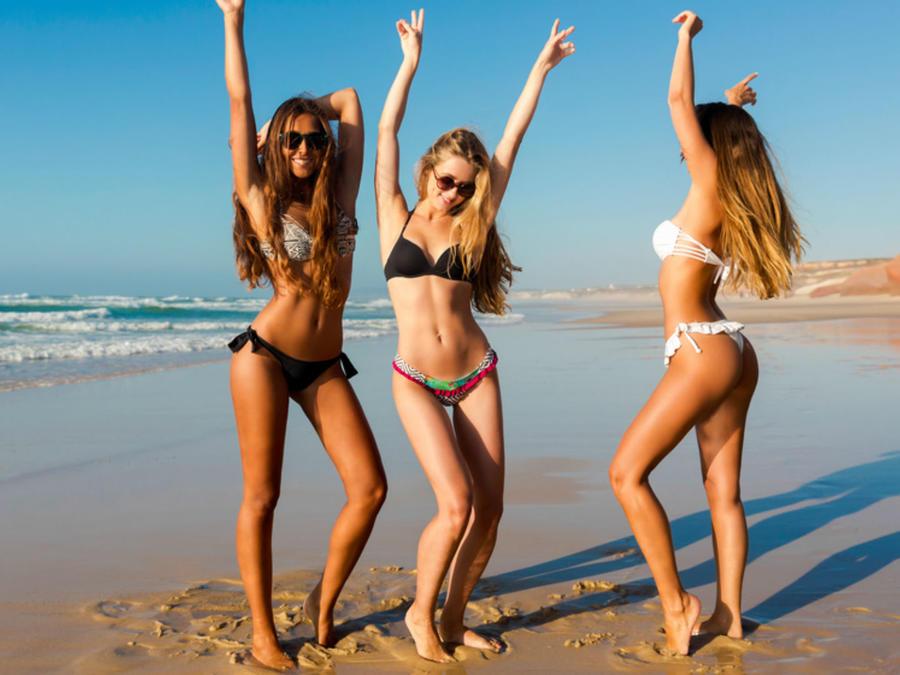 Tres mujeres divirtiéndose en la playa en bikini