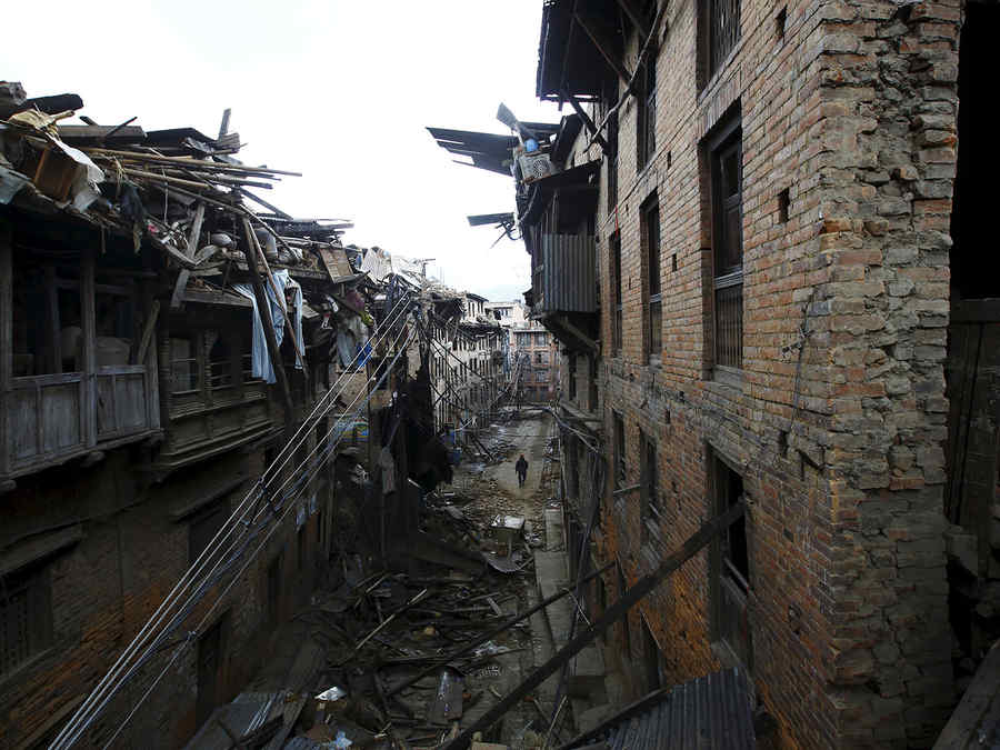 Damaged houses are pictured as a man walks along deserted street after the earthquake in Bhaktapur
