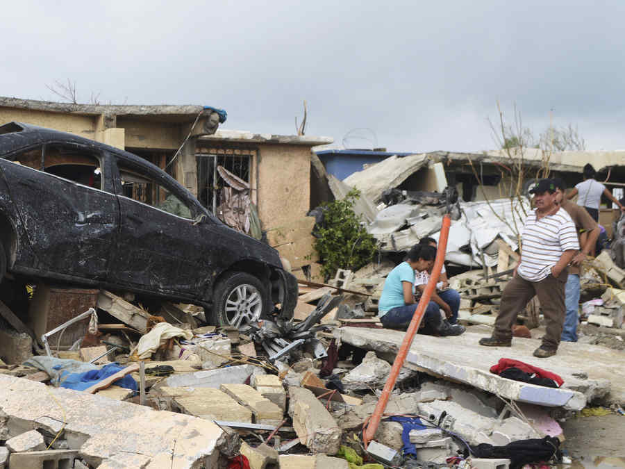 Residents stand outside their damaged house after a tornado hit the town of Ciudad Acuna