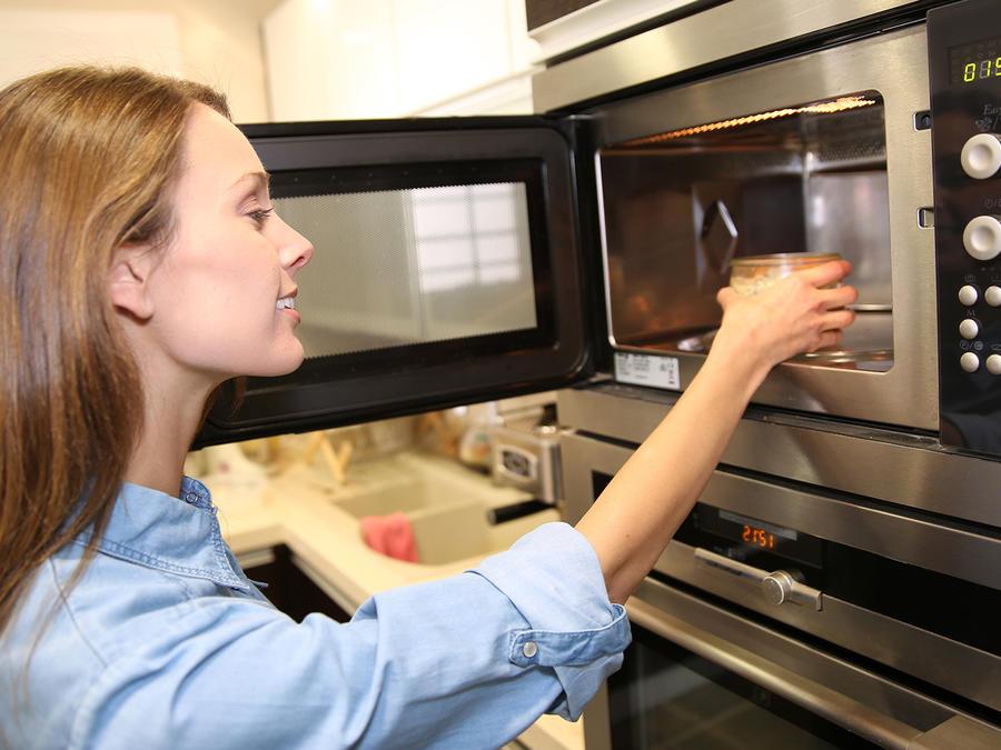mujer utilizando un microondas