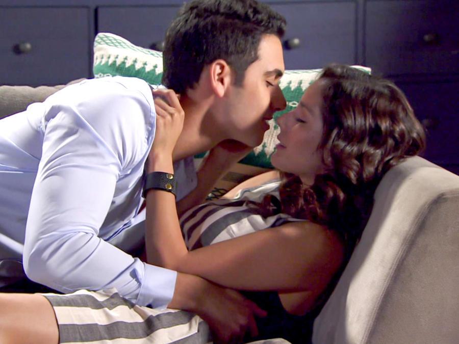 Alejandro Speitzer y Oka Giner besándose en un sofá en Bajo El Mismo Cielo