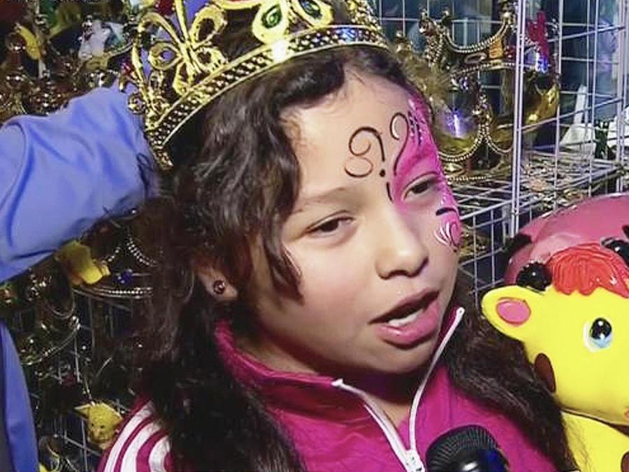 niña con corona hablando