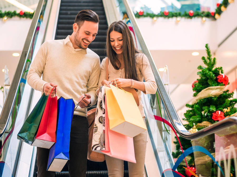 Una pareja carga los paquetes de las compras navideñas.