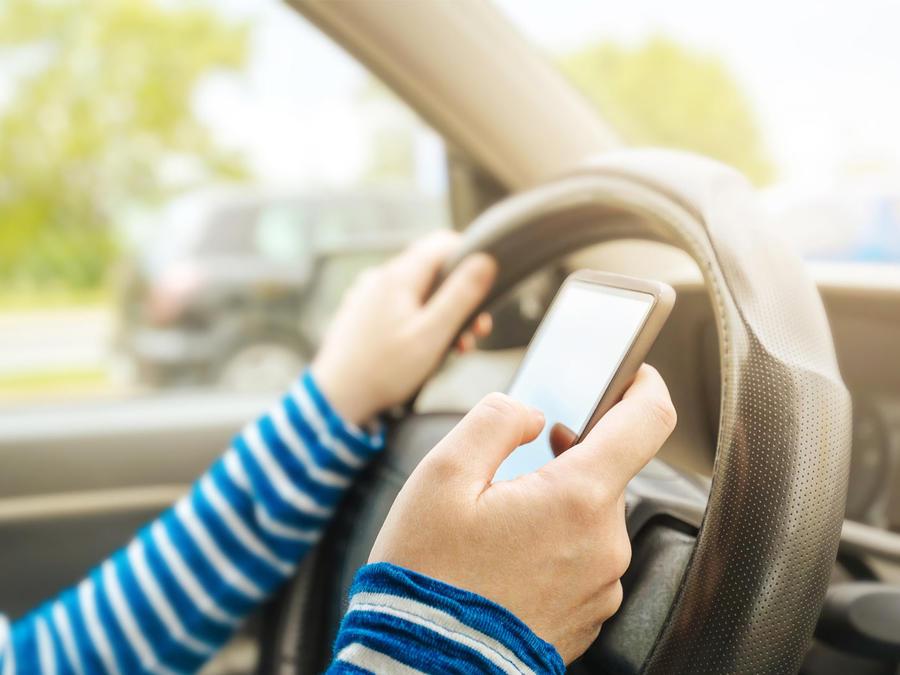 mujer textea mientras maneja