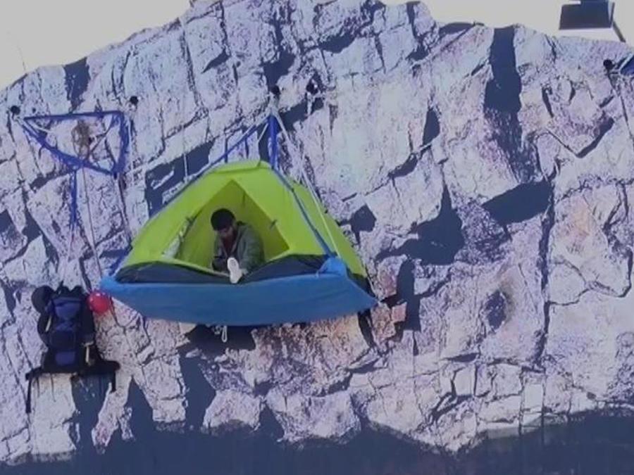 escalador cuelga casa de campaña