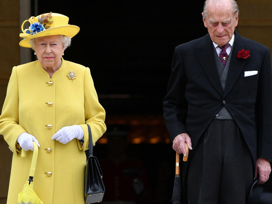 Britain's Queen Elizabeth and Prince Philip observe a minute's silence to honour the victims of the attack on Manchester Arena at the start of a garden party at Buckingham Palace in London