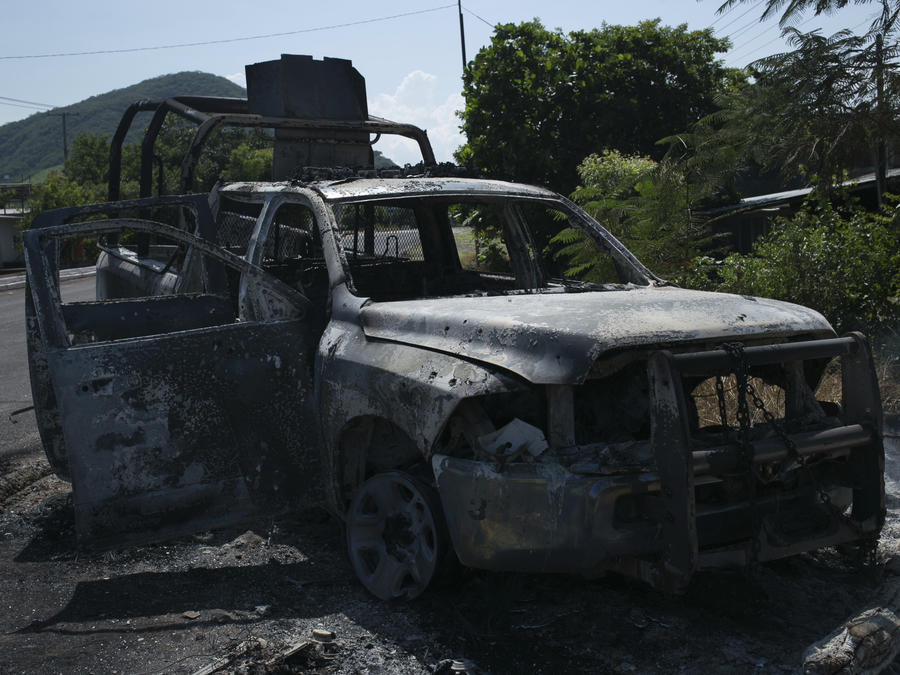 A charred truck that belong to Michoacan state police stands on the roadside after it was burned during an attack in El Aguaje, Mexico,
