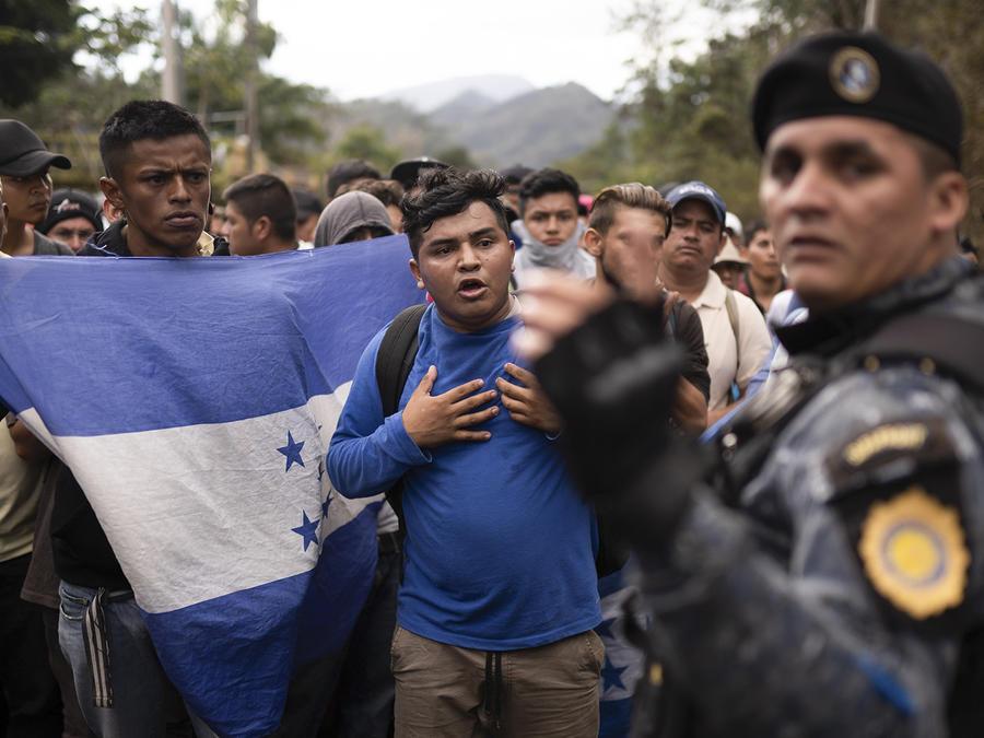 La caravana de migrantes hondureños frente a un oficial de policía en Guatemala.