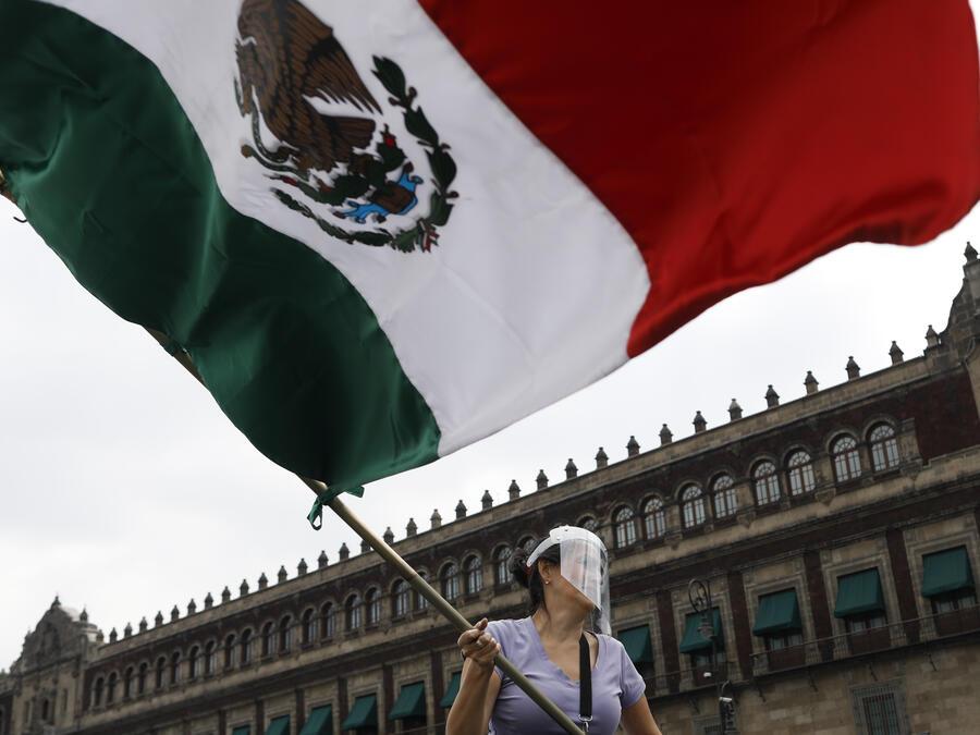 Una mujer que llevaba un protector facial ondea una bandera mexicana frente al Palacio Nacional durante una protesta de una caravana de autos llamando al presidente mexicano Andrés Manuel López Obrador a renunciar, en la Ciudad de México
