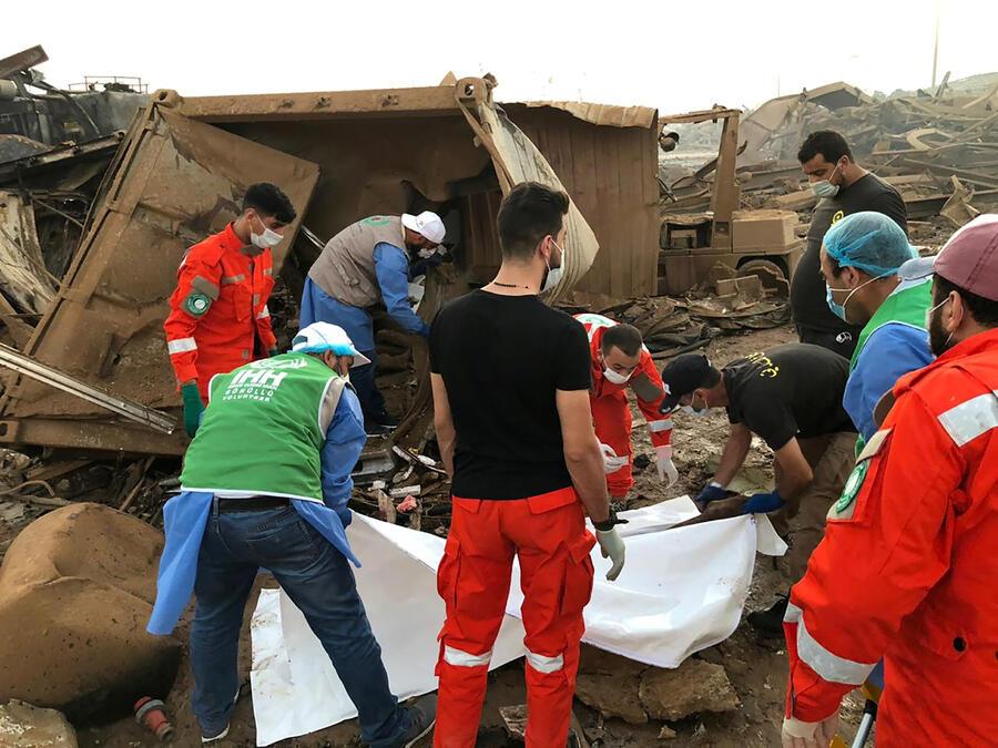 Los miembros de la Fundación de Ayuda Humanitaria de Turquía (IHH) ayudan a los médicos locales a llevar a una víctima de la explosión del martes en el área del puerto de Beirut, Líbano, el 5 de agosto de 2020.