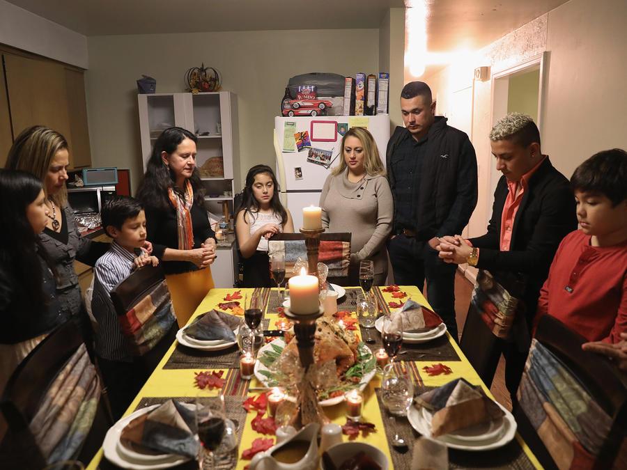 Los inmigrantes centroamericanos y sus familias rezan antes de la cena de Acción de Gracias el 24 de noviembre de 2016 en Stamford, Connecticut.