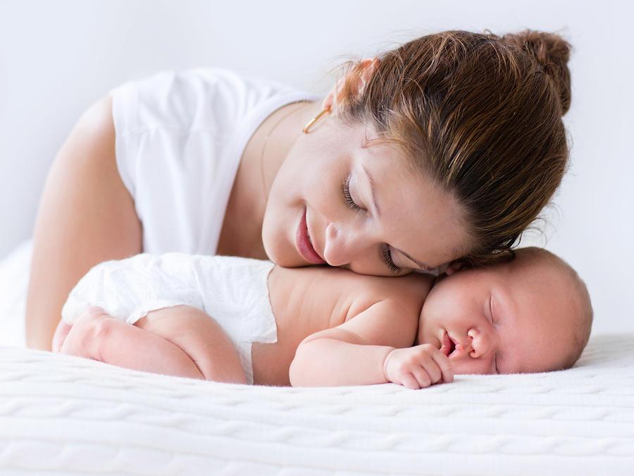 Madre joven y recién nacido en habitación blanca