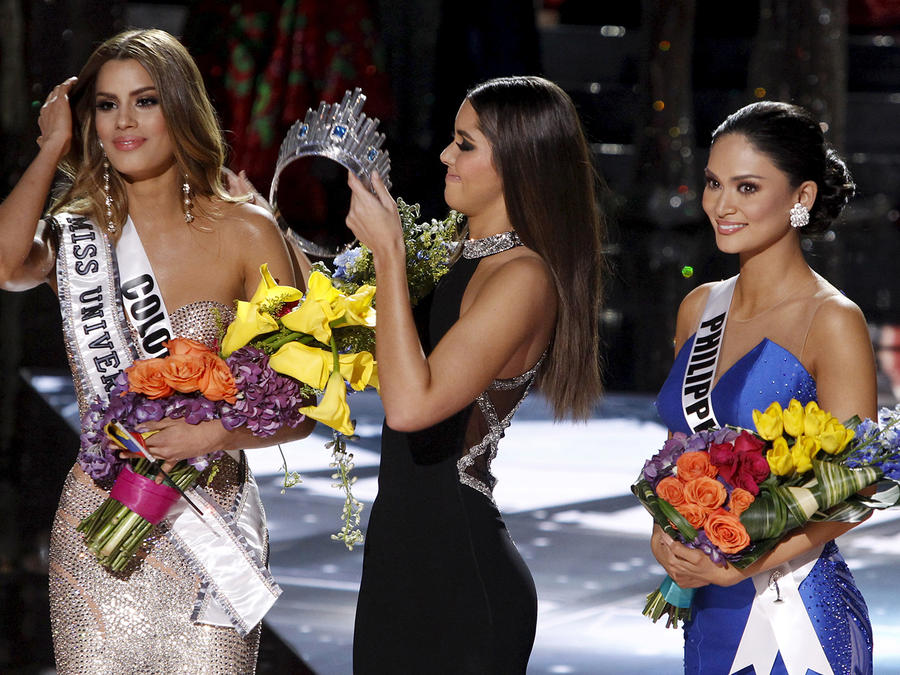 Miss Colombia Gutierrez stands by as Miss Universe 2014 Paulina Vega transfers the crown to winner Miss Philippines Wurtzbach during the 2015 Miss Universe Pageant in Las Vegas