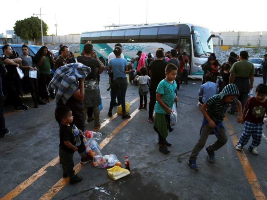 Foto del 16 de julio de 2019, migrantes en el exterior de un centro para migrantes en el Puente Internacional 1, antes de ser trasladados en bus desde Nuevo Laredo a Monterrey, en México.