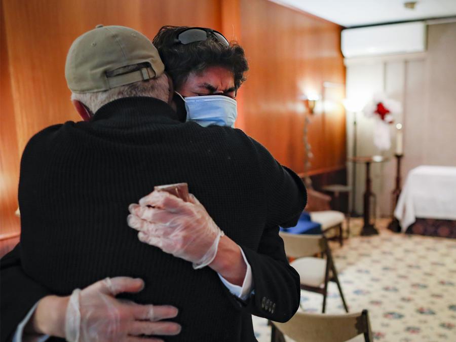 Leonardo Cabaña llora en los brazos de su amigo, Raphael Benevides, junto al ataúd de su padre, Héctor Miguel Cabaña, quien murió de COVID-19 en Brooklyn, Nueva York.