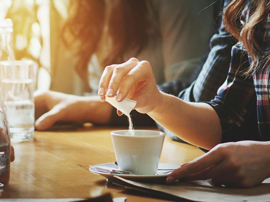 Mujer agregando edulcorante artificial a su taza de café