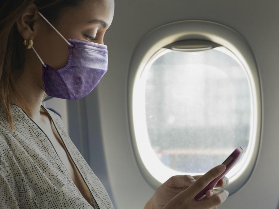 Mujer usando mascarilla durante vuelo en avión