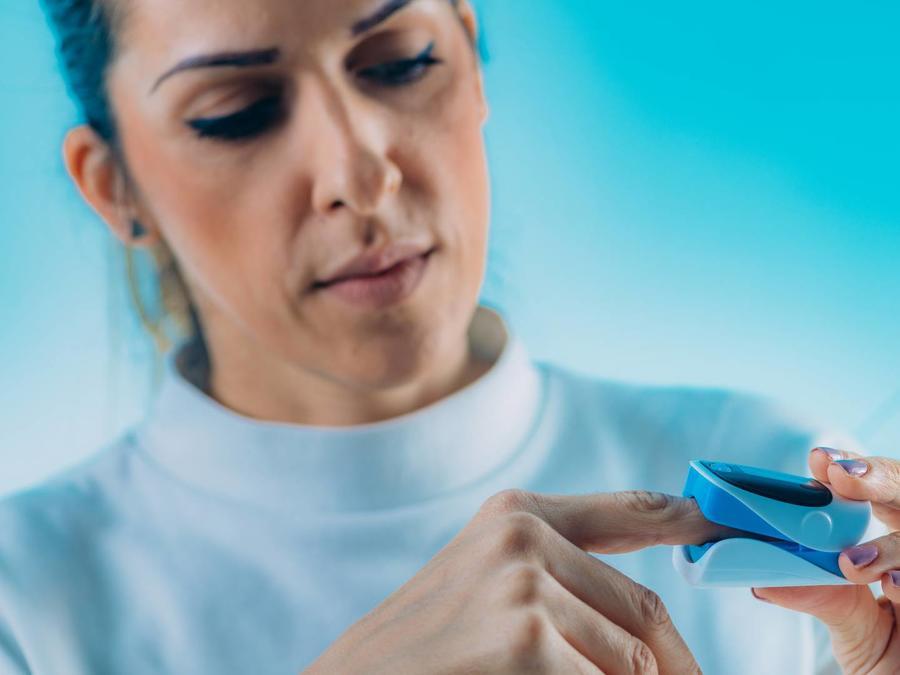 Mujer midiendo sus niveles de oxígeno en la sangre