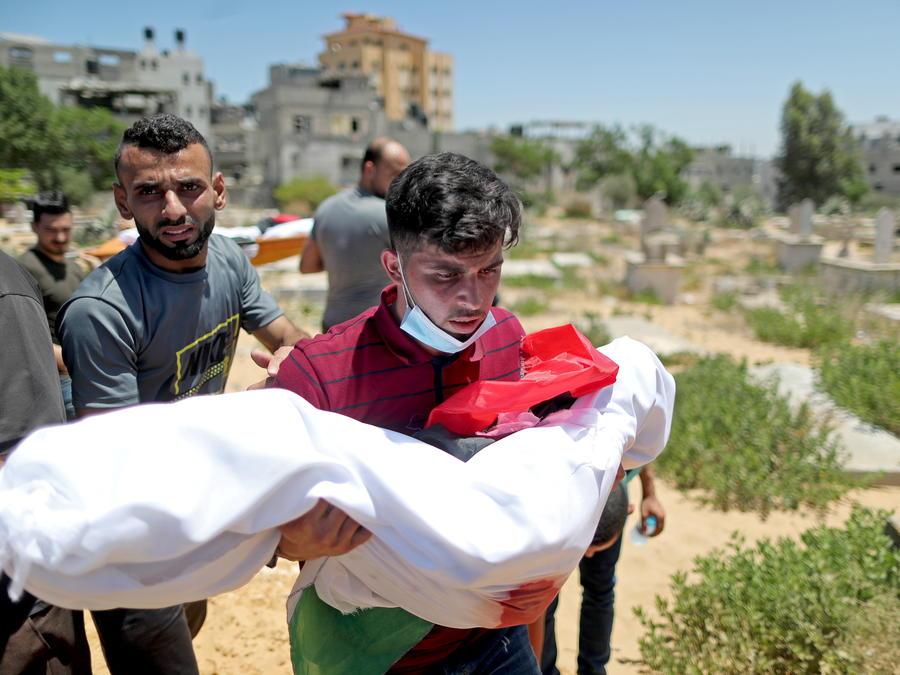 Un hombre lleva el cuerpo de un niño palestino.