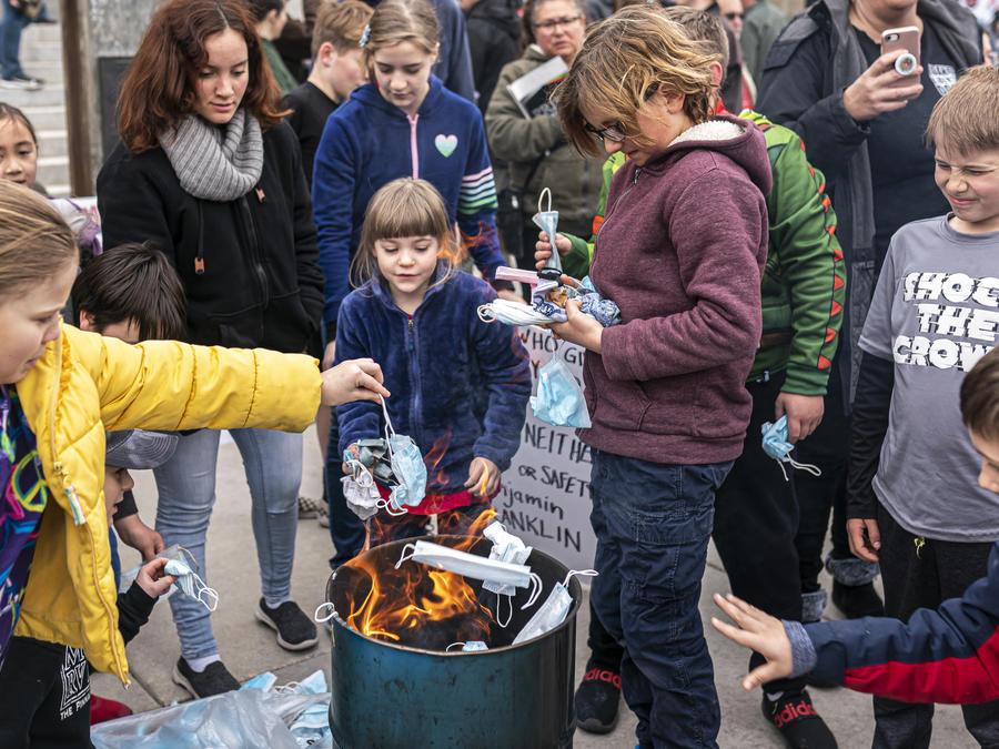 Manifestantes contra las restricciones por el COVID-19 queman mascarillas frente al Capitolio de Idaho, el sábado 6 de marzo de 2021.